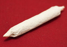 Marijuana. A macro shot of a joint over red Stock Photography
