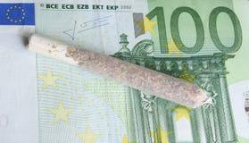 Marijuana cigarette on money Stock Images