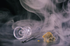 Marijuana extraction concentrate aka wax crumble on dark background with smoke stock image