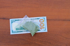 Marijuana i paket- och för dollar 100 räkning på trätabellen Royaltyfria Foton