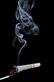 Marijuana joint. A joint being lit by a match, isolated on a black background stock photography