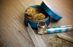 Marijuana Joint and Pipe on Warm Lighted Table. Marijuana Joint, Paper, Grinder and Pipe on Warm Lighted Table stock photography