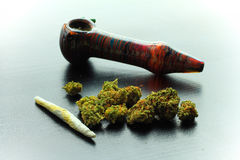 Marijuana Joint and Pipe. Laying on a shiny black wooden surface. Focus on the foreground Stock Photo