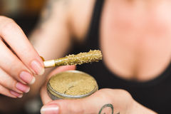 Marijuana Joint with Wax, Oil, and Kief. Woman holding a cannabis or marijuana joint in her hand. Joint is dipped in oil or wax and sprinkled with kief & x28;THC Royalty Free Stock Photo