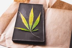 Marijuana leaf with edible dark chocolate block and cannabis brownie with ganja top view isolated on white background.  royalty free stock images