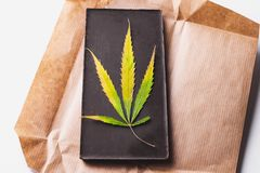 Marijuana leaf with edible dark chocolate block and cannabis brownie with ganja top view on white background.  royalty free stock photography