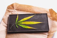 Marijuana leaf with edible dark chocolate block and cannabis brownie with ganja top view on white background.  royalty free stock photo
