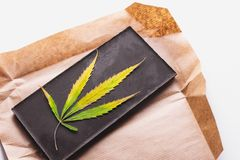 Marijuana leaf with edible dark chocolate block and cannabis brownie with ganja top view on white background.  royalty free stock photos