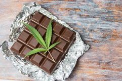 Marijuana leaves on top of chocolate. Marijuana leaves on top of dark chocolate Stock Photos