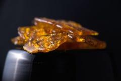 Marijuana oil concentrate aka shatter isolated on black backgrou. Close up detail of marijuana oil concentrate aka shatter isolated on black background Royalty Free Stock Image