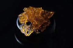 Marijuana oil concentrate aka shatter isolated on black backgrou Stock Photo