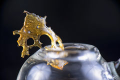 Marijuana oil concentrate aka shatter isolated with glass rig on. Close up detail of marijuana oil concentrate aka shatter isolated on black background with Stock Photos
