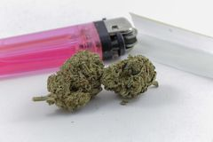 Marijuana slår ut med rullande legitimationshandlingar och en tändare royaltyfri foto