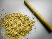 Marijuana a terra e un Cigarillo su un fondo grigio Fotografia Stock
