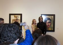 Marilyn Manson Art Exhibit. Marilyn Manson and girl-friend promoting his art exhibition posing besides one of his famous paitings Stock Images