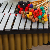 Marimba with coloured mallets. A marimba with a lot of colored mallets on it, and musical notes in the background Stock Photography