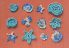 Marin- bakgrund med beståndsdelar för bomullsspetsvirkninghantverk: stjärnor skal, blommor som göras av mjukt akrylullgarn Virkad Arkivfoto
