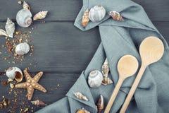 Marin- bakgrund Trä gjord sked, servett, snäckskal Fotografering för Bildbyråer