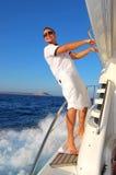 Marin détendant heureusement le yacht de bateau à voiles Images libres de droits