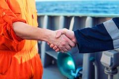 Marin- leverant?raff?rsmanhandshaking med arbetaren p? skeppet arkivfoto