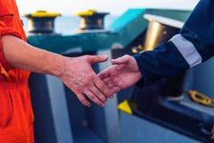 Marin- leverant?raff?rsmanhandshaking med arbetaren p? skeppet royaltyfri foto