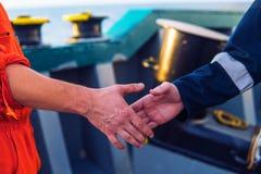 Marin- leverant?raff?rsmanhandshaking med arbetaren p? skeppet fotografering för bildbyråer