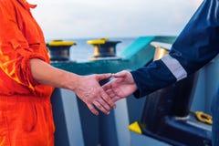 Marin- leverant?raff?rsmanhandshaking med arbetaren p? skeppet royaltyfria foton