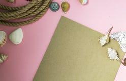 Marin- semesterbakgrund f?r sommartid med massor av sn?ckskal, kiselstenar, nautiskt rep p? rosa bakgrund Det finns en tillg?ngli royaltyfri fotografi