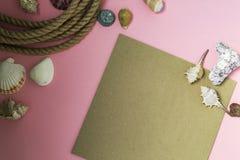 Marin- semesterbakgrund f?r sommartid med massor av sn?ckskal, kiselstenar, nautiskt rep p? rosa bakgrund Det finns ett ark av pa arkivbilder