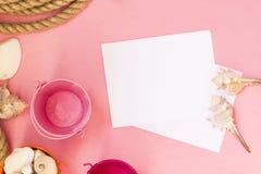 Marin- semesterbakgrund f?r sommartid med massor av sn?ckskal, kiselstenar, nautiskt rep p? rosa bakgrund Det finns ett ark av pa royaltyfri fotografi