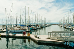Marina. Shilshole Bay Marina in Seattle, Washington, on Puget Sound showing gangway leading to pier and two rows of pleasure craft separated by water. Blue sky stock photography