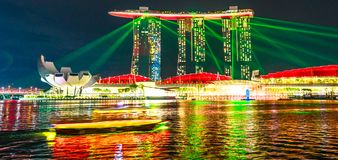Marina Bay laser show. Singapore - April 27, 2018: colorful laser show at night at Marina Bay Sands Hotel Casino and ArtScience Museum with boat on the waters of Stock Image
