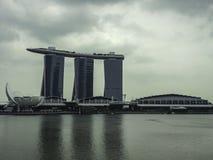 Marina Bay met meest spectaculaire hotelachtergrond in de bewolkte dag in de donkere toon van het beeld Stock Foto's