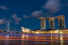 Marina Bay Sands and Singapore Flyer as seen from Fullerton Bay at night. With ferry boats moving in the foreground Stock Image