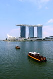 Marina bay sands of singapore. Many tourists have a tour on the traditional passenger boat of Singapore river. There is famous Marina Bay Sands resort structure Stock Photos