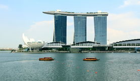 Marina bay sands of singapore. Many tourists have a tour on the traditional passenger boat of Singapore river. There is famous Marina Bay Sands resort structure Stock Photography