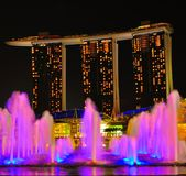 Marina Bay Sands. A view of marina bay sands with sky park towers by night at the background. In the foreground are the lighted water fountain playing with the Stock Photography