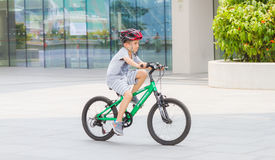 Marina bay, Singapore - Sep 9: Kid playing on bike for fun. on Sep 9, 2015 in Marina bay,Singapore. Marina bay, Singapore - Sep 9: Kid playing on bike for fun stock photo