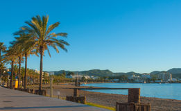Marina & bay in St Antoni de Portmany, Ibiza, Balearic Islands, Spain. Calm water along boardwalk & beach in warm, late day sun. Late afternoon golden sun falls royalty free stock images