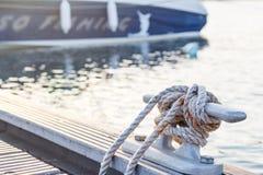 Marina bitt to tie mooring ropes. Marina bitt to tie white rusty mooring ropes for boat mooring closeup on sunset stock photo