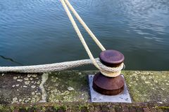 Mooring bitt in a harbor. Marina bollard bitt to tie mooring ropes for yachts mooring Royalty Free Stock Image
