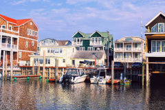 Marina in Cape May NJ US. Marinas and houses with red and green roofs reflected in the water. spring time in Cape May NJ royalty free stock image