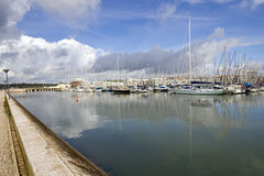 Marina in the clouds. View of the marina with the reflection of clouds in the still water.  Shot in Lagos, Portugal Stock Photography