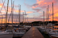 Marina in Desenzano del Garda sunrise. Colorful sunrise over the yacht marina in Desenzano del Garda in Italy, tranquil scene with sail boats, quay and lamp post Stock Photography