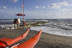 Lifeguard tower and rowing boat on the shoreline. MARINA DI MASSA, ITALY - AUGUST 17 2015: Lifeguard tower and rowing boat on the shoreline with rough seas Stock Photo