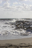 Waves crashing into rocks in Marina di Massa, Italy. MARINA DI MASSA, ITALY - AUGUST 17 2015: Waves crashing into rocks in Marina di Massa, Italy royalty free stock images