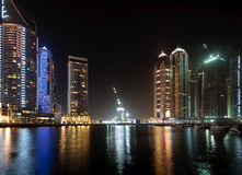 Marina in Dubai at night. Modern skyscrapers reflected in the marina in Dubai with a contruction underway in the center stock images