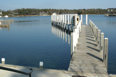 Marina in Early Spring. The ice has thawed.  Calm water reflects the symmetry of a marina's pier Stock Images