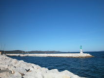 Marina entrance and pier. Seascape of marina entrance and pier with a small lighthouse on it, France Stock Image