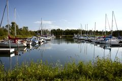 Marina full of sailboats on a nice sunny summer day. View of a marina on Lake Superior full of boats and sailboats. Clear blue sky and calm water reflecting the Royalty Free Stock Images